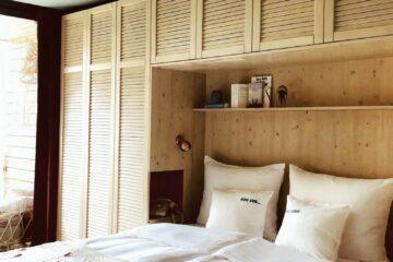Bett mit weißer Bettwäsche und pinkem Hippie-Zeichen an grauer Decke