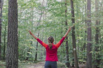 Frau streckt beide Arme im Wald in die Höhe