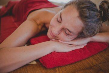 Frau liegt entspann auf Handtuch