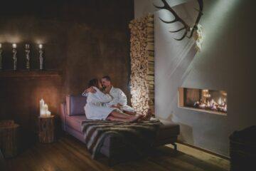 Paar in Bademantel umarmt sich auf Daybed am Kamin