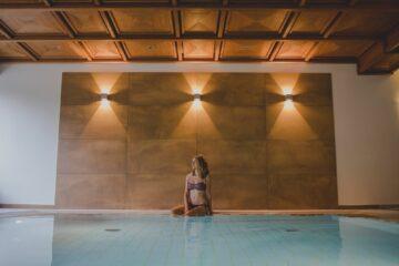 Frau sitzt am Beckenrand des Indoor-Pools