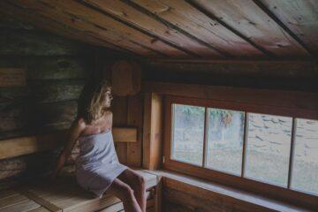 Frau sitzt mit Handtuch in Sauna
