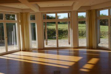 Heller Rundraum mit Parkett und breiter Fensterfront in den Garten