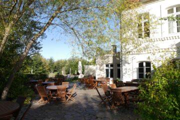 Terrasse mit Bänken und Stühlen unter Bäumen
