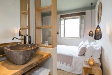 Zimmer mit offenem Fenster und Bett und Stein-Waschschüssel