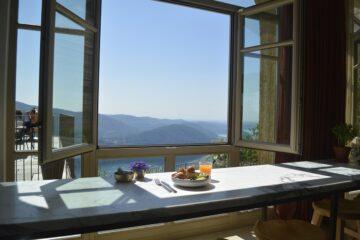 Tisch am offenen Fenster mit Frühstücksteller und Blick über die Berge