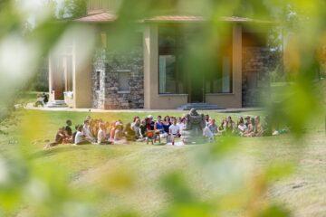Gruppe sitzt im Garten vor Buddha-Statue
