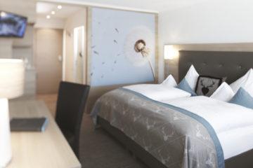 Zimmer mit Bett und Pusteblumewand
