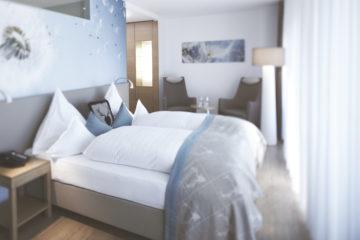 Zimmer mit Doppelbett und Pusteblumentapete