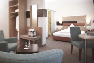 Zimmer mit Bett und zwei Sesseln und Schreibtisch