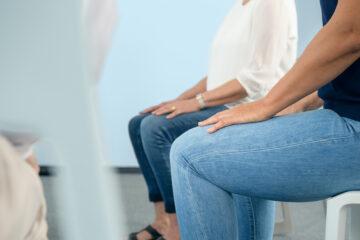 Meditierende Sitzhaltung auf Stuhl mit Händen auf den Schenkeln