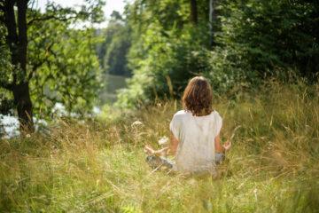 Frau meditiert in Wiese
