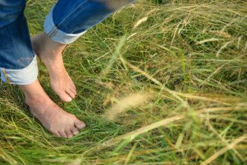 Nackte Füße gehen über Wiese