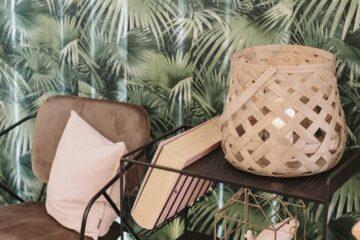 Palmtapete mit Korblampe und Stuhl in Retro-Optik
