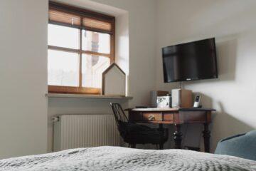Zimmer mit Holzsekretär und Bambuskampe an der Decke