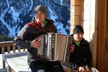 Mann spielt Zieharmonika auf Berghütte