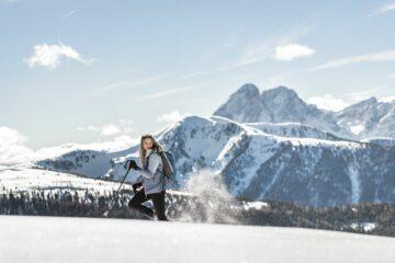 Lächelnde Frau beim wandern durch den Schnee