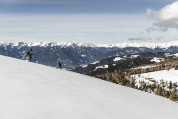 Mann und Frau laufen verschneiten Hügel hinab
