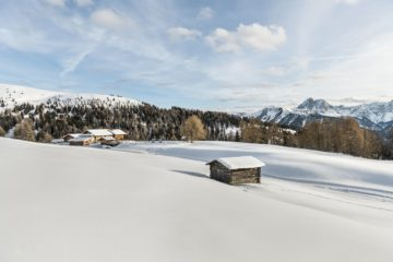 Blick über verschneite Ebene zum Gebirge