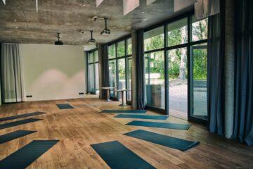 Yogaraum mit Fensterfronten und Yogamatten in Petrol