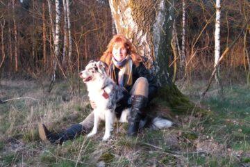 Frau sitzt mit Hund am Baum