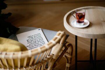 Teetasse mit Teebeutel auf Tisch und Stuhl mit Zeitschrift