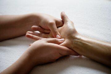 Frau massiert Hand