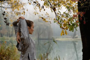 Frau dehnt sich am Wasser im Wald