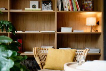 Bücherregal und Rattansessel mit gelbem Kissen