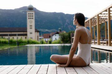 Frau sitzt am Pool und blickt auf Kirche