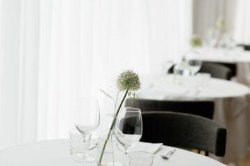 Gläser mit Vase und weißer Blume auf Tisch