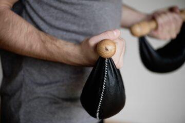 Mann hält Sandgewichte in Lederbeuteln