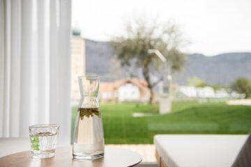 Glaskaraffe mit Wasser und Kräutern