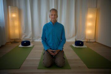 Trainer in meditativer Haltung auf Matte