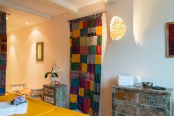 Raum mit buntem Vorhang und gelber Massageliege