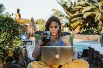 Frau sitzt mit Laptop am Pool