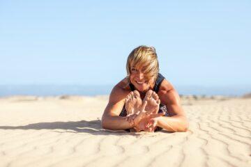 Frau sitzt im Sand und lacht