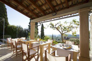 Terrasse mit Tischen und Stühlen und Inselpanorama