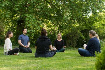 Gruppe meditiert auf Rasen