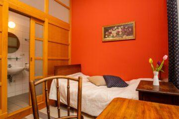 Bett an orangener Wand und antike Möbel