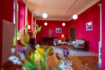 Pink gestrichener Raum mit Flügel und antikem Sofa und Sessek