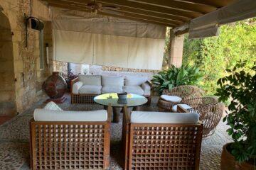 Lounge-Sofa und Stühle am Garten überdacht