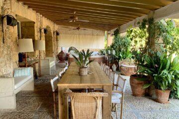 Langer Holztisch mit Stühlen auf Steinfliesen