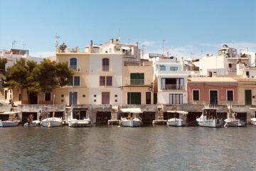 Boote am Hafen vor Häusern und Kaimauer