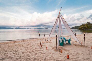 Tisch mit Stühlen am Strand mit Fackeln
