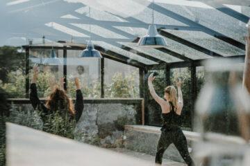 Gruppe macht Yoga unter Glasdach