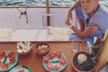 Frau sitzt an Deck am Tisch mit Tellern mit Broten