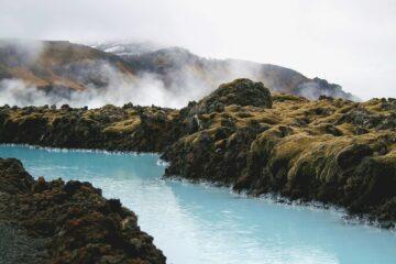 Hellblauer Fjord und neblige Hügel
