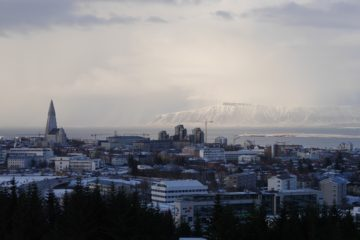 Blick über Stadt zum beschneiten Berg