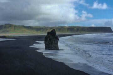 Fels am schwarzen Strand und grünen Bergriesen